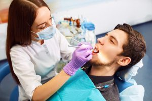 The dentist checks the mouth of the patient.