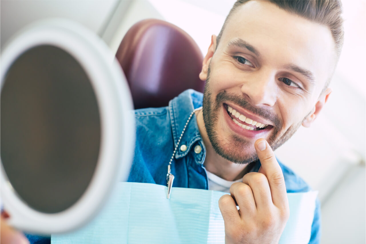 The patient looks at his teeth in the mirror.