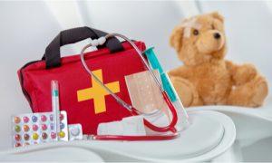 A baby first aid kit beside a cute teddy bear.