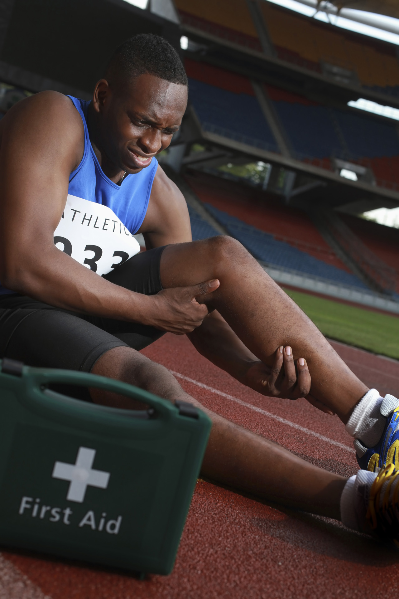 Male-athlete-lying-on-track-clasping-leg-in-pain