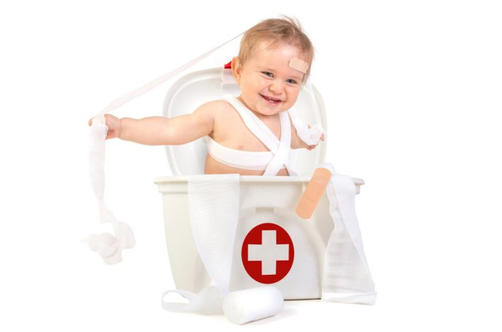 A cute little boy inside the baby first aid kit.